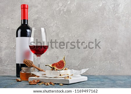 Gourmet appetizer of white brie cheese or camembert with fresh figs, nuts, honey and red wine on wooden cutting board and gray concrete background