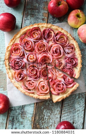 Gourmet apple tart. Open pie with red apple roses and cream filling served with organic apples on shabby blue wooden table above view