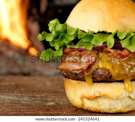 Gourmet bacon cheeseburger with lettuce and tomato in front of the fire