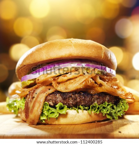 gourmet bacon hamburger with golden background and copy space composition