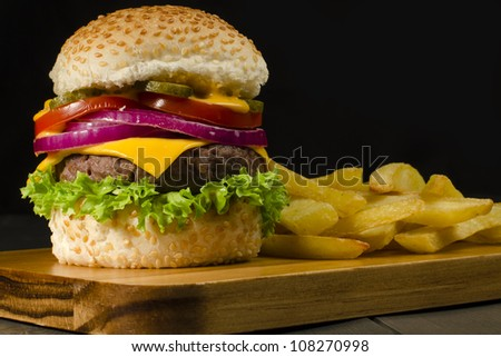 Gourmet Cheeseburger  amp  Chips - Burger and thick cut chips on a black    Gourmet Cheeseburgers