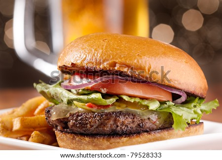 gourmet cheeseburger with mug of beer in background