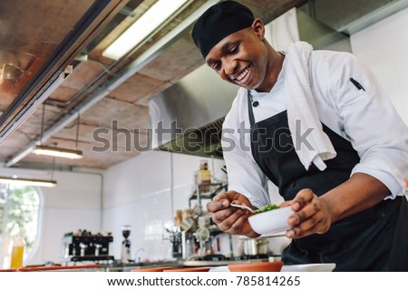 Gourmet chef in uniform cooking in a commercial kitchen. Happy male cook wearing apron standing by kitchen counter preparing food.
