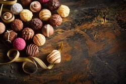 Gourmet chocolate Valentines still life with a large selection of luxury handmade chocolates with a single heart shaped bonbon on a twirled ribbon symbolising love and romance with copy space