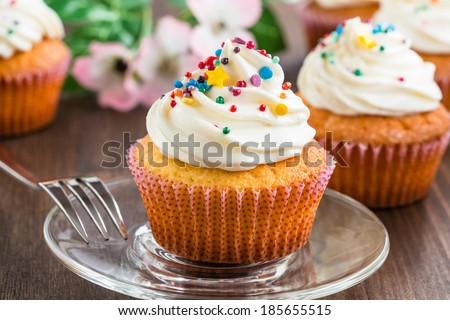 Gourmet cupcakes with white buttercream frosting and sprinkles on wooden background