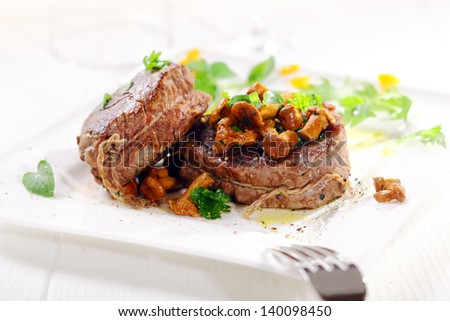 Gourmet dinner of thick juicy medallions of fillet steak tied with string topped with wild mushrooms and served garnished with herbs on a white platter