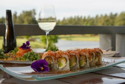 Gourmet. Elegant restaurant. Raw salmon sushi rolls beautiful dish presentation and table set up in the restaurant gallery, with the golf course and lake background view.