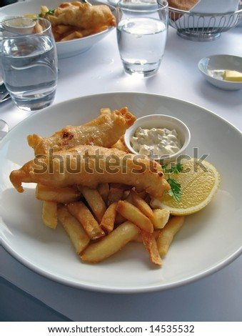 Gourmet fish and chips with a slice of lemon and tartar sauce.