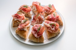 gourmet focaccia with prosciutto of Parma ham, mozzarella and rosemary sprigs, eight tasty slices of pizza on a white plate