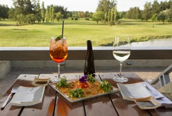 Gourmet food. Elegant sushi restaurant. Outside table set up and dish presentation. Raw salmon sushi plate with white wine and drink, with a beautiful golf course and lake view in the background.