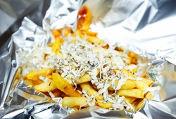 Gourmet French fries with melted gorgonzola cheese served in tin foil for delivery.Delicious golden potato chips with burned cheese in foil delivered from take away menu in fastfood restaurant