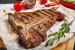 Gourmet Grill Restaurant Steak Menu - T-Bone Beef Steak on Wooden Background. Black Angus Prime Beef Steak. Beef Steak Dinner