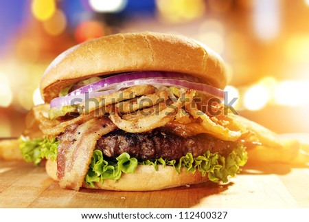 Gourmet hamburger with fried onion straws and cityscape background.