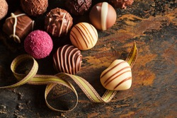 Gourmet handmade heart shaped chocolate praline on a twirled gold ribbon with a selection of speciality chocolates over rustic wood for Valentines day