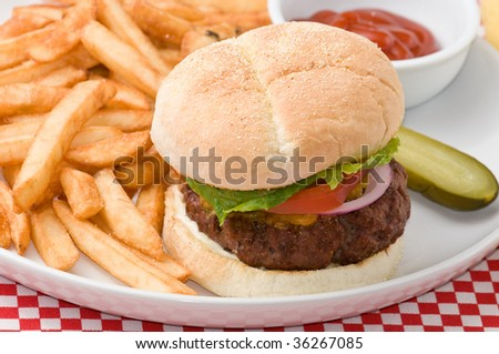 Gourmet homemade hamburger with cheddar cheese, lettuce, tomato, onion, pickle, french fries and soda