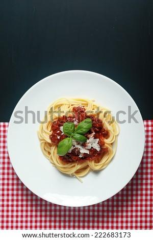 Gourmet Italian Pasta Food on White Round Plate Placed Between Red White Checked and Black Background.