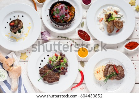 Gourmet meat meals assortment flat lay. Top view on restaurant table with menu of tasty grilled snacks. Buffet, appetizing, delicious food, barbecue concept #604430852
