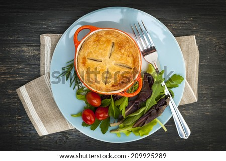 Gourmet meat pie with garden salad served on plate from above