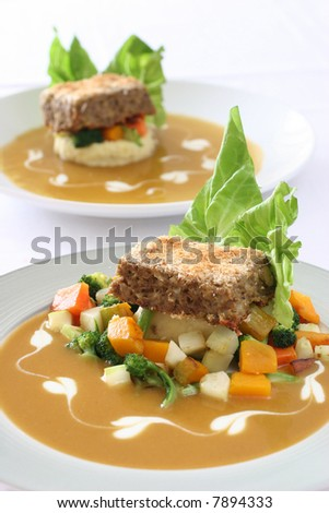 Gourmet meatloaf on a bed of vegetables and mash garnished with trimmed lettuce