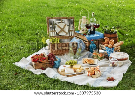 Gourmet picnic spread with fresh fruit, cheese, wraps, crusty bread, wine and dessert surrounding a wicker hamper on green grass in a park