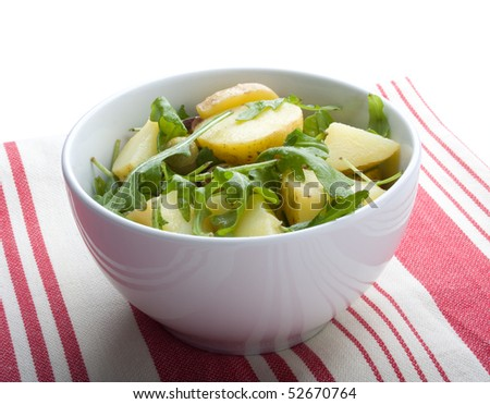 Gourmet potato salad with rocket lettuce (rucola), on red and white tablecloth - stock photo