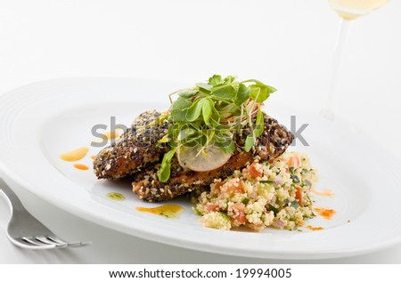Gourmet salmon dish garnished with vegetables, white background.