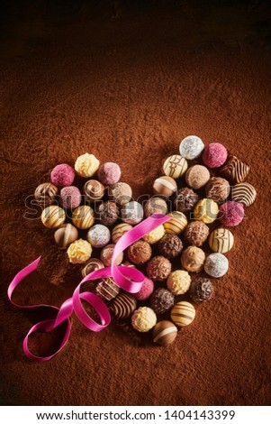 Gourmet selection of hand made chocolates arranged as a heart on a background of cocoa powder with twirled pink ribbon and vignette symbolic of love #1404143399