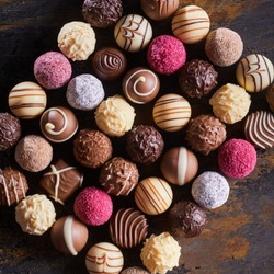 Gourmet speciality chocolate bonbons or pralines arranged in a neat rectangle on rustic wood table viewed top down
