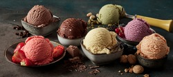 Gourmet summer dessert of artisanal or craft ice cream made with fresh berries, macaroons, coffee beans, pistachio nuts and chocolate served in bowls in a wide angle banner