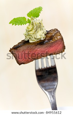 Gourmet Time,piece of a grilled steak with herb butter on a fork