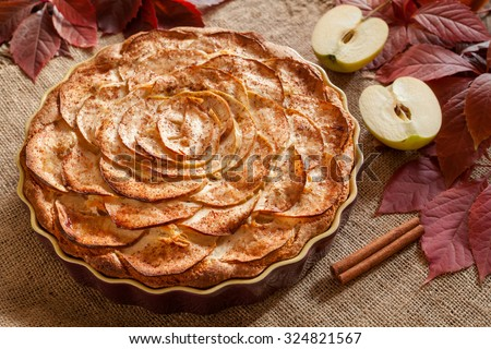 Gourmet traditional holiday apple pie sweet baked dessert food with cinnamon and apples on vintage background. Autumn decor. Rustic style and natural light.