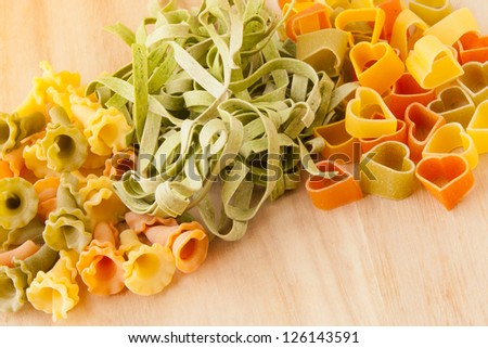 Gourmet variety of  Italian pasta on wooden background. Gigli pasta, spinach fettuccine and heart shape pasta.