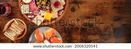 Gourmet wine snacks panorama. A glass of red wine and a platter with olives, blue cheese and other cheeses and hams. Salmon sandwiches and crackers. Antipasti or tapas on a rustic wooden background Stock photo ©