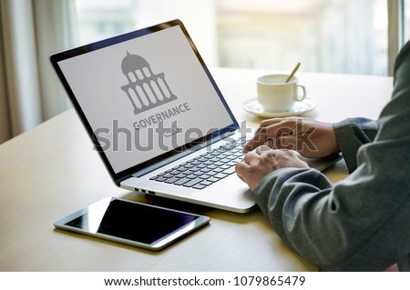 GOVERNANCE and building, Authority Computing Computer Laptop with screen on table Silhouette and filter sun
