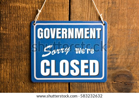 "Government Shutdown concept. "" Sorry we're closed "" sign in blue and white, with the word ""GOVERNMENT"". Rustic wooden wall background."