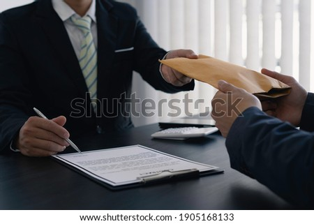 Government tax officials are accepting citizens of bribes wrapped in brown envelopes. To open the way for annual tax evasion, the concept of bribery officials to avoid taxes. ストックフォト ©