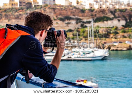 Gozo, Malta, May 2018 - Young photographer taking photo at ferry #1085285021
