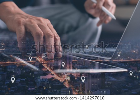GPS map, pin address location on mobile apps. Double exposure of man hand using digital tablet searching target place on night cityscape while working on laptop computer.