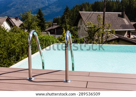 Grab bars ladder in blue swimming pool in a garden in Austria