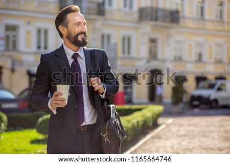 Grab some coffee. Cheerful smiling businessman standing outdoors while going to work #1165664746