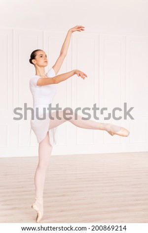 Grace and beauty in every move. Full length of beautiful young ballerina in white tutu dancing in ballet studio