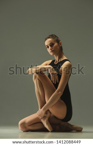 Graceful ballet dancer or classic ballerina dancing isolated on grey studio background. Showing flexibility and grace. The dance, artist, contemporary, movement, action and motion concept. #1412088449
