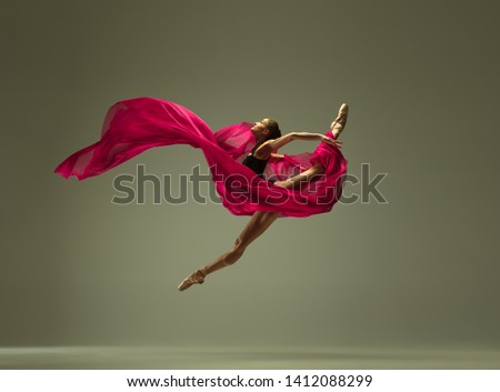 Graceful ballet dancer or classic ballerina dancing isolated on grey studio background. Woman with the pink silk cloth. The dance, grace, artist, contemporary, movement, action and motion concept.