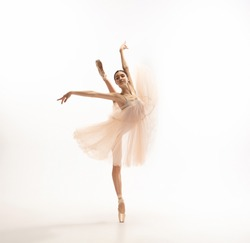 Graceful classic ballerina dancing, posing isolated on white studio background. Tender peach cloth. The grace, artist, movement, action and motion concept. Looks weightless, flexible. Fashion, style.