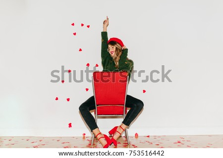 Graceful girl in red high heel shoes sitting on chair and laughing. Indoor portrait of excited woman in green sweater and black pants posing with hand up on white background.