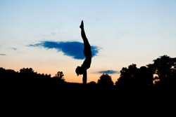 Graceful Gymnast Dancer Balances with Pointed Toe silhouette in handstand Against sunset sky with sunburst