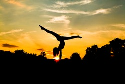 Graceful Gymnast Dancer Balances with Pointed Toe silhouette in handstand upside down with split Against sunset sky with sunburst