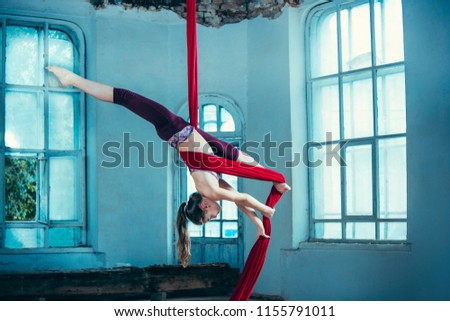 Graceful gymnast performing aerial exercise with red fabrics on blue old loft background. Young teen caucasian fit girl. The circus, acrobatic, acrobat, performer, sport, fitness, gymnastic concept #1155791011