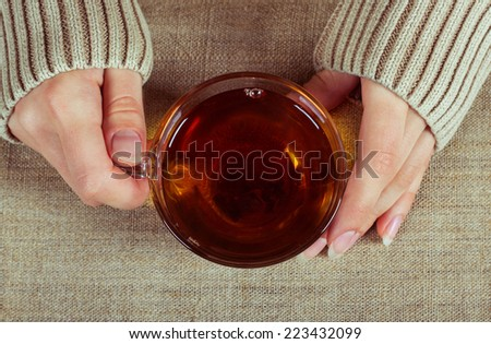 Graceful hands of a girl with a cup of tea and a long-sleeved shirt, symbolizing the comfort of home