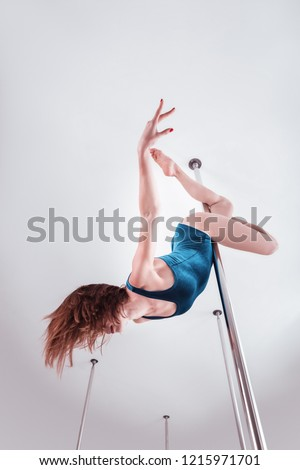 Graceful movements. Young skillful pole dancer feeling good while showing amazing graceful movements #1215971701
